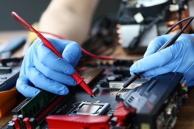 Le mani stanno riparando il dispositivo elettronico, saldando