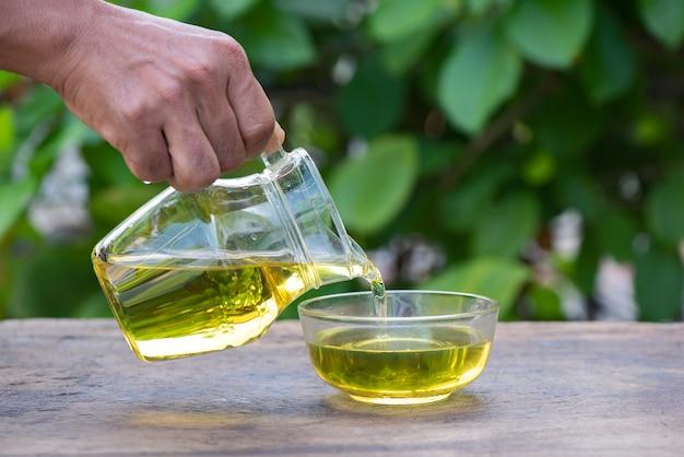 Le mani stanno versando l'olio d'oliva nella brocca