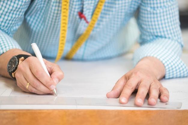 Le mani su misura segnano il disegno sulla carta del mestiere per fare i modelli.