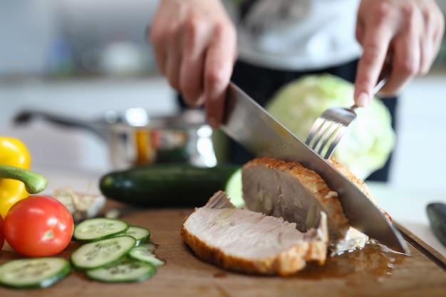 Le mani tagliano la carne suina e le verdure al forno pronte
