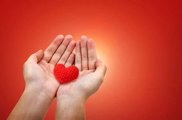 Le mani tengono cuori rossi