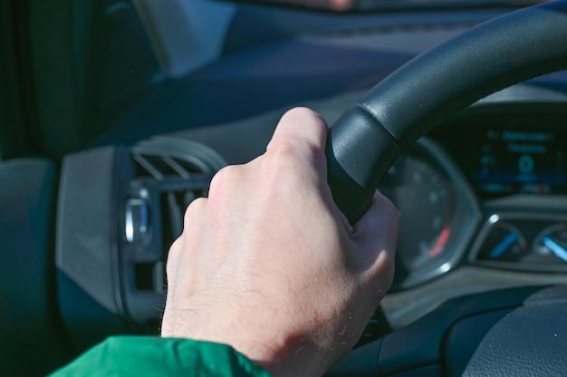 Le mani tengono il volante di un'auto, i batteri sul volante di un'auto