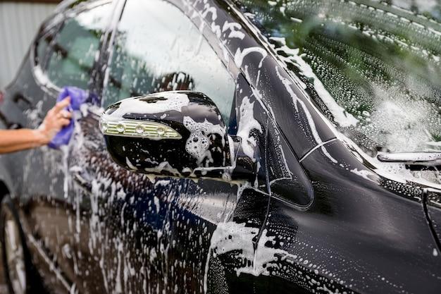 Le mani tengono la spugna per lavare l'automobile. messa a fuoco selettiva. dettagli auto. pulizia con spugna e panno. pulizia del lavoratore. soluzione di lavaggio automatico per la pulizia