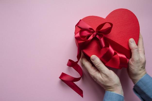 Le mani tengono o danno il contenitore di regalo rosso a forma di cuore con il nastro rosso