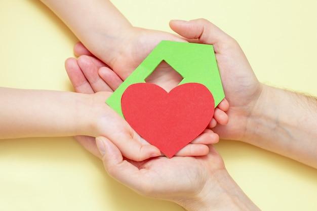 Le mani tiene la casa del libro verde con cuore rosso.