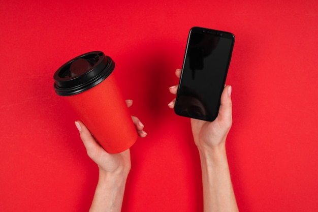Le mani tiene una tazza di caffè e un telefono isolati su rosso