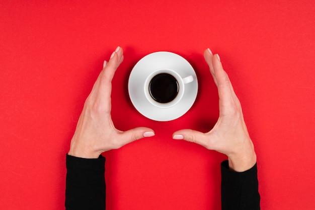 Le mani tiene una tazza di caffè isolata su rosso