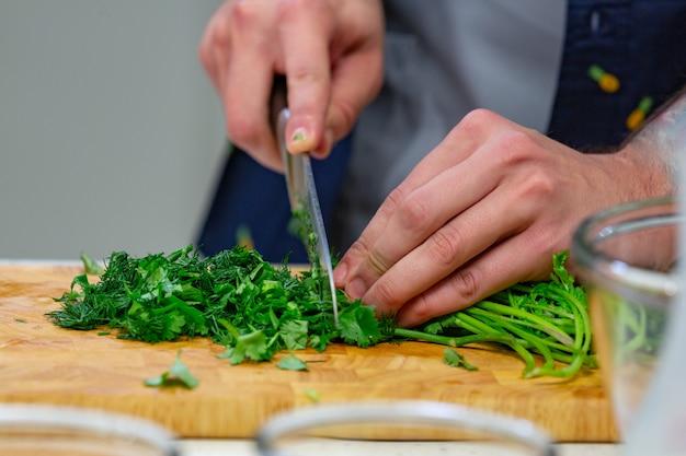 Le mani umane con il coltello d'acciaio tagliente che tagliuzzano le foglie verdi del prezzemolo sul bordo di legno