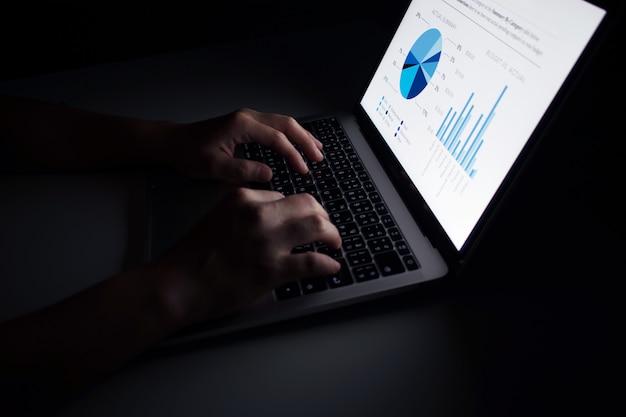 Le mani utilizzano i display dei grafici finanziari dei laptop nelle stanze buie.