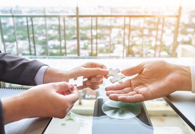 Le mani vicine collegano due puzzle. concetto di business, successo e strategia.