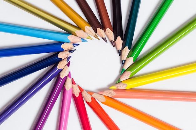Le matite colorate giacciono in cerchio su uno sfondo bianco