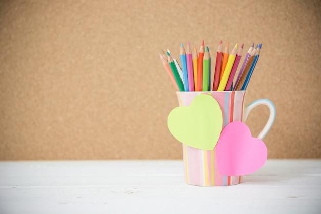 Le matite di colore di natura morta in tazza variopinta sulla tavola di legno e post-it per inseriscono il vostro testo