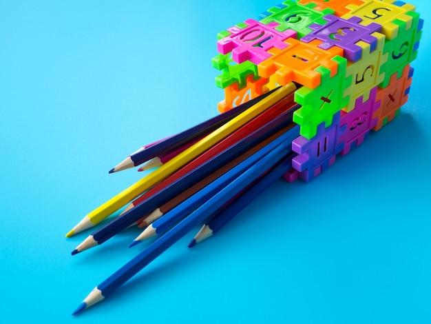Le matite di colore in colorfull del supporto di matita fanno il numero di puzzle della forma su fondo blu