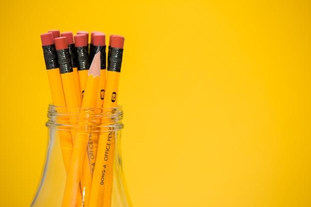 Le matite in un vaso di vetro, sfondo giallo