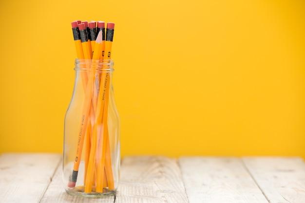 Le matite in un vaso di vetro su un pavimento di legno, sfondo giallo