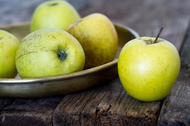 Le mele gialle fresche si trovano in un piatto d'ottone antiquato