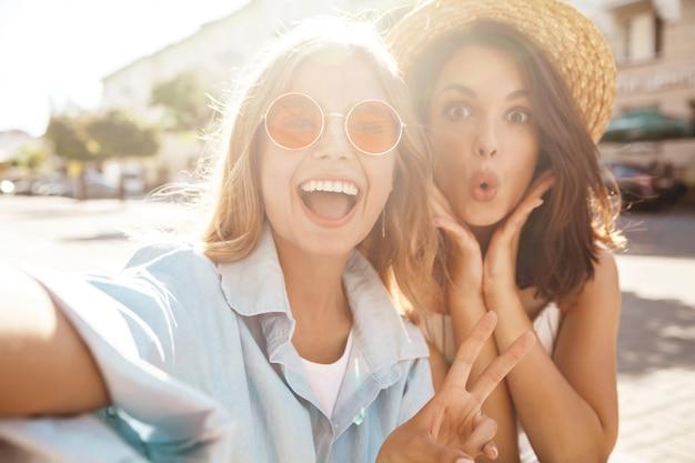 Le migliori amiche che indossano abiti eleganti e fanno selfie per strada