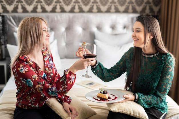 Le migliori amiche che si godono la giornata con cibo e vino