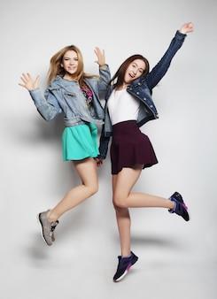 Le migliori amiche di ragazze giovani hipster saltano