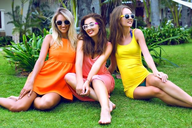 Le migliori amiche di ragazze sexy si divertono in vacanza in un paese tropicale caldo esotico, indossando abiti da spiaggia vivaci a vita bassa brillante, emozioni felici, sorridendo e ridendo, festa in giardino, relax, ballo, gioia.