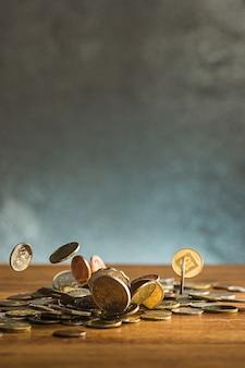 Le monete d'argento e d'oro e le monete che cadono sul tavolo di legno