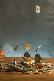 Le monete d'argento e d'oro e le monete che cadono sulla parete di legno