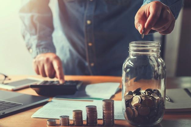 Le monete della tenuta della mano dei soldi di risparmio del ragioniere che mettono in brocca di vetro