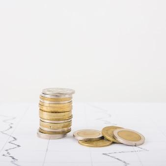 Le monete impilano sul tavolo bianco