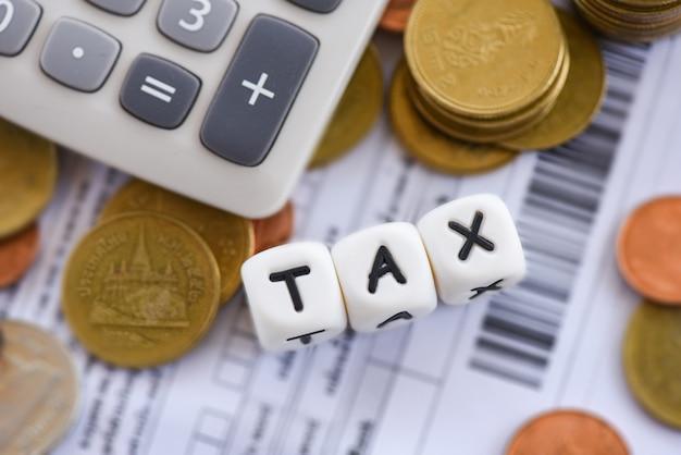 Le monete impilate di concetto e del calcolatore di imposta sulla carta della fattura della fattura per la tassa di tempo che riempie hanno pagato il pagamento di debito alle finanze di affari dell'ufficio
