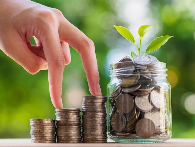 Le monete in vaso di vetro e la mano della donna fanno un passo sulla pila di moneta sul fondo della sfuocatura
