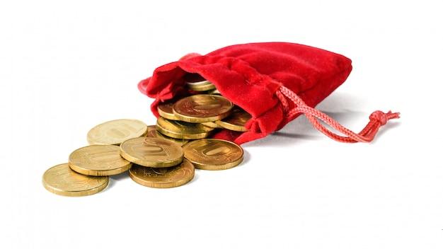 Le monete sono versate da una borsa rossa isolata su un bianco.