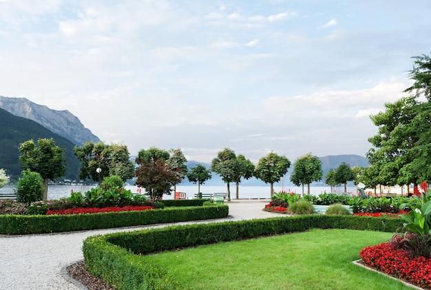 Le montagne, il lago e il terrapieno della città con alberi tagliati, arbusti, prato e aiuole.