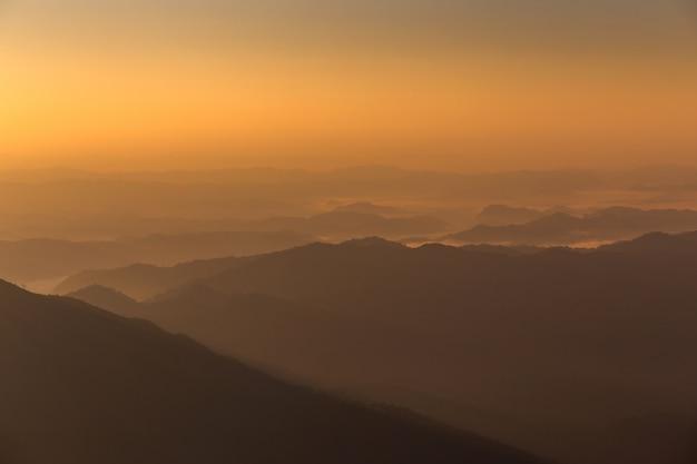 Le montagne osservano l'orizzonte e le nuvole di alba arancio di fondo.