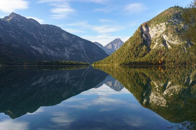 Le montagne si riflettono nell'acqua di un lago di montagna. la foto è stata scattata nelle alpi a plansee in austria