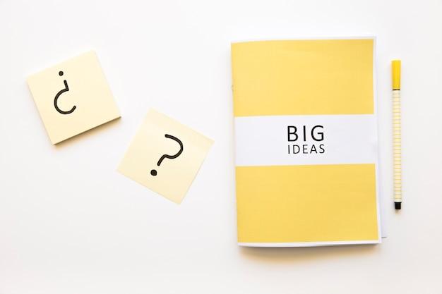 Le note appiccicose con il punto interrogativo firmano vicino alle grandi idee diario e penna