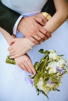 Le nuove spose del primo piano mostrano le loro fedi nuziali