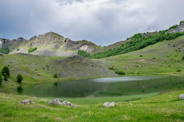 Le nuvole di pioggia si stanno avvicinando al lago di montagna.