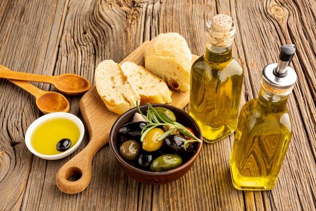 Le olive ad alto angolo mescolano bottiglie di pane e olio