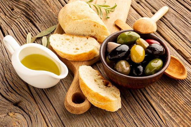 Le olive ad alto angolo mescolano pane e piattino di olio