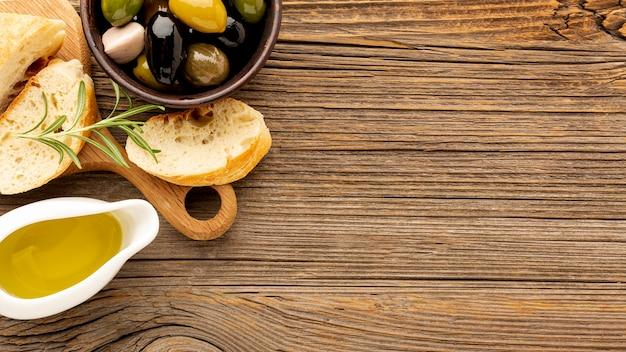 Le olive dell'angolo alto mescolano il piattino del pane e dell'olio con lo spazio della copia