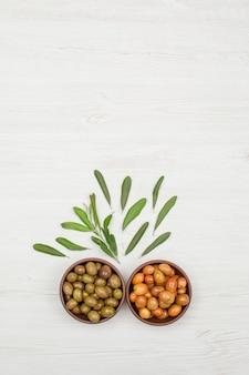 Le olive verdi e giallo-rosa in un'argilla lancia con la vista superiore delle foglie di olivo su legno bianco