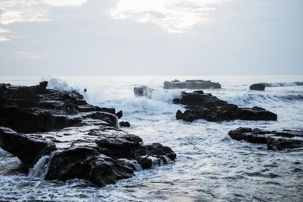 Le onde dell'oceano si infrangono contro le rocce. spruzzi onde dell'oceano al tramonto.