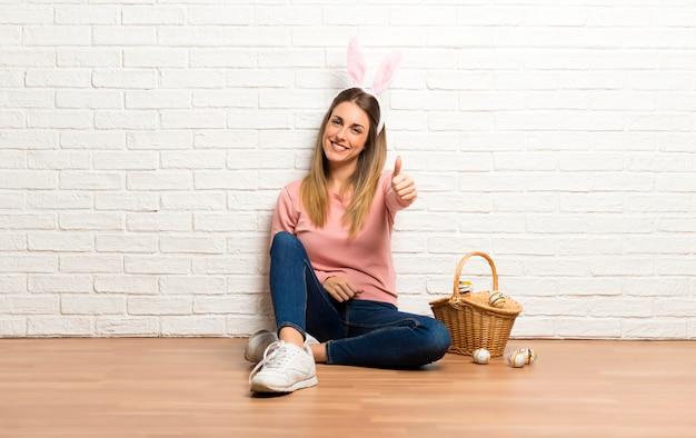 Le orecchie d'uso del coniglietto della giovane donna per le feste di pasqua dando pollici aumentano il gesto e sorridere