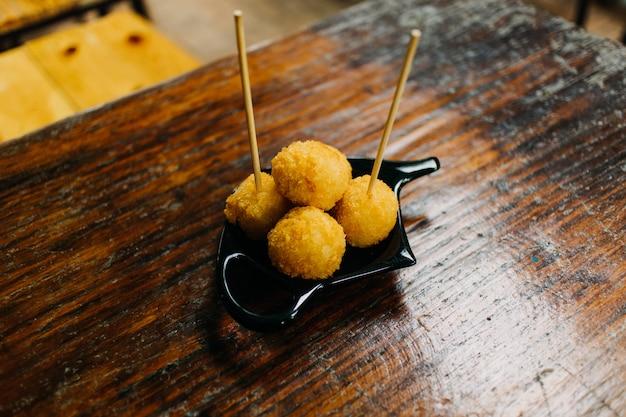 Le palle del formaggio fritto sono servito sulla tavola di legno nel caffè.