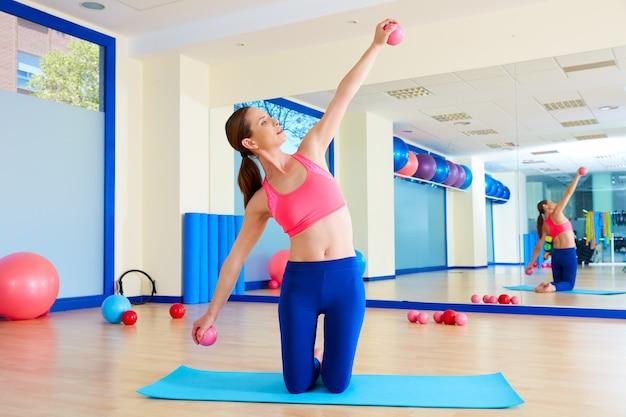 Le palle di sabbia della donna di pilates esercitano l'allenamento alla palestra