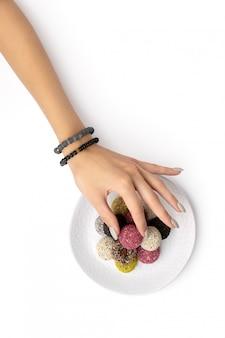 Le palle variopinte dell'energia delle caramelle del vegano sul piatto con la mano della donna hanno isolato il bianco