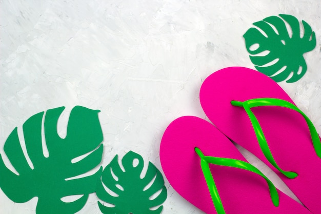 Le pantofole rosa di vista superiore e il monstera di carta lascia lo spazio della copia