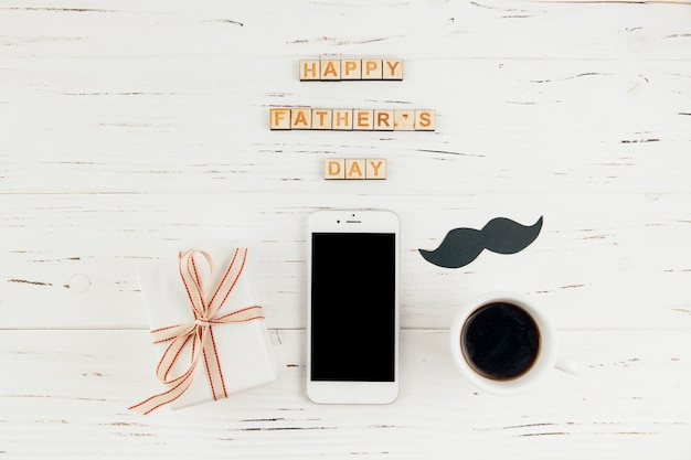 Le parole felici del giorno di padri si avvicinano allo smartphone con il regalo e la tazza della bevanda