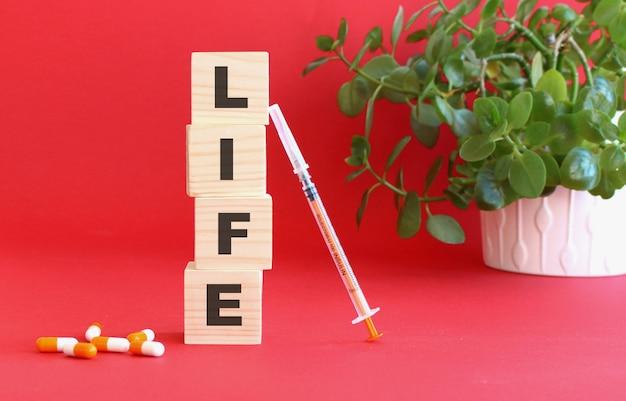 Le parole life fatte di cubi di legno accanto a farmaci