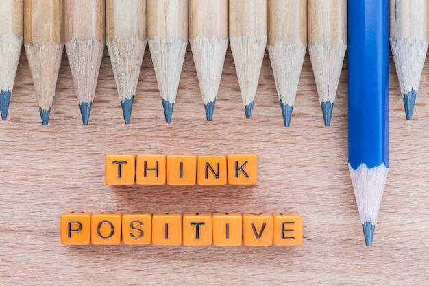 Le parole pensano positivamente sul tavolo di legno con il gruppo delle matite.